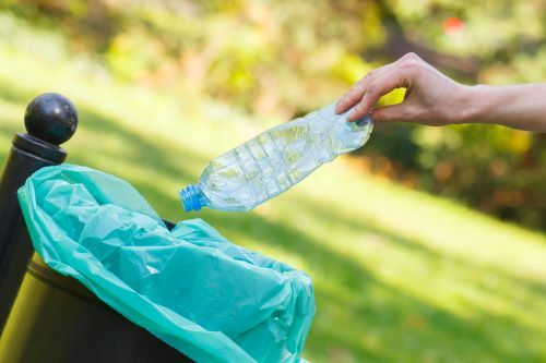 hand-of-woman-throwing-bottle-into-recycling-bin-l-PKKLYTX.jpg