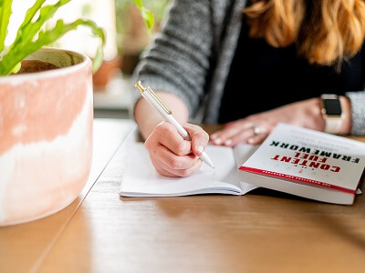 woman-write-pen-room-table-houseplant.jpg