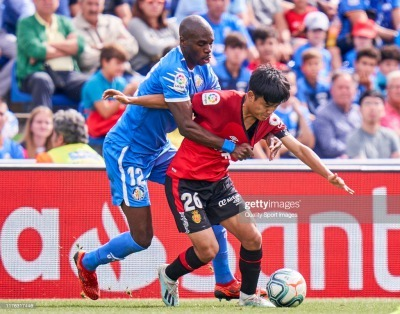 Allan Nyom of Getafe CF battle for the ball with Kubo takefusa