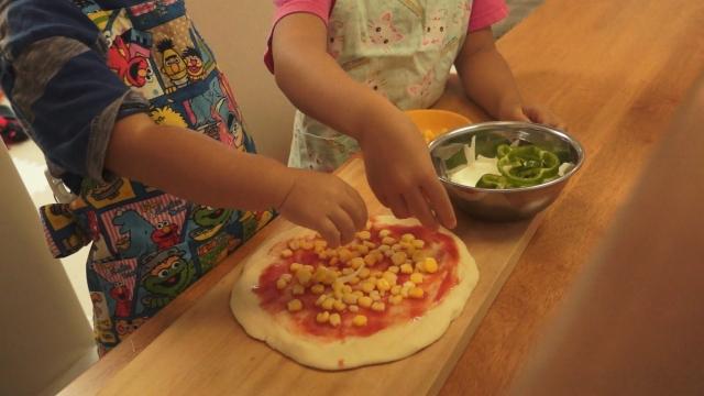 子供たちがピザの具を盛り付け