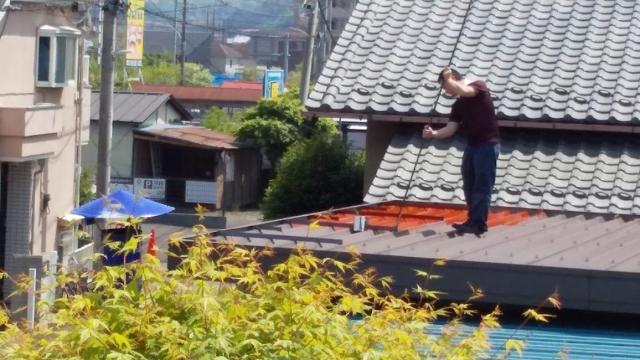 物置の屋根にペンキを塗り始める