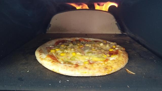 ピザ窯でピザを焼く